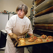 A baker (Elaine Sayles) removes a tray of fat rascals (a local variety of scone) from the oven at Hovingham bakery, North Yorkshire, UK