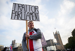 © Licensed to London News Pictures. 31/10/2019. London, UK. A protester holds a placard saying 'Traitor Parliament' as he stands in Parliament Square on what would have been the United Kingdom's last day as a member of the European Union. The date of Brexit had been moved to January 31, 2020 after MPs failed to pass Prime Minister Boris Johnson's withdrawal agreement. Photo credit: Peter Macdiarmid/LNP