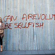 Graffiti (can a revolution be selfish) by the boarded up central post office of Athens