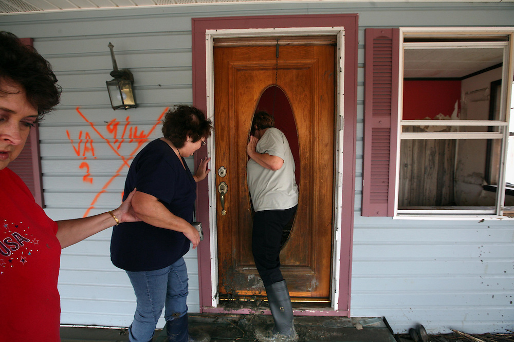 Lifelong Sabine Pass residents Betty Adkins, center, and Lois Berg, right, survey the damage to Lois's home after of Hurricane Ike Friday September 19, 2008.