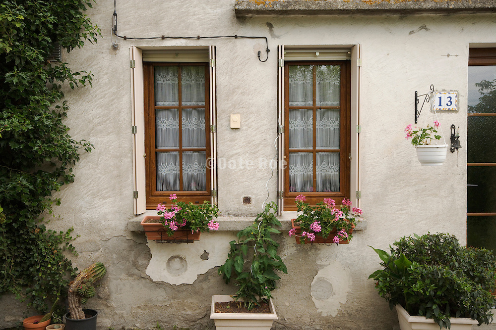 front of house with potted plants under the windows