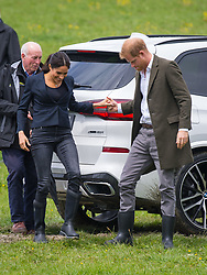 The Duke of Sussex helps the Duchess of Sussex as she steps over a puddle as they attend a dedication of an area of bush to the Queen's Commonwealth Canopy, in Redvale on the North Shore, on day three of the royal couple's tour of New Zealand.