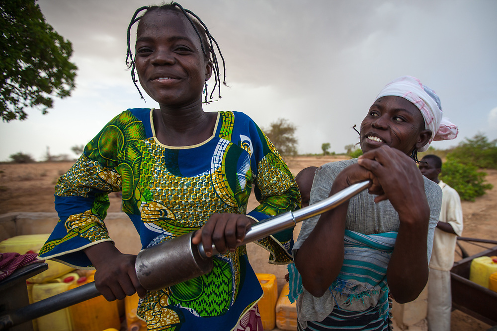 Two women laugh while they work a water pump in Niger