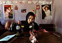 KABUL,AFGHANISTAN - SEPT. 10:  Afghan girls learn to sew in a program run through the UN Habitat September 10, 2002 in Kabul, Afghanistan.  Old magazines of western and Indian models decorate the walls fo the workshop. (Photo by Ami Vitale/Getty Images)