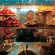 A young man seen throught the window at  'Paratha walli gulli' , one of the most famous places for parathas in old Delhi.