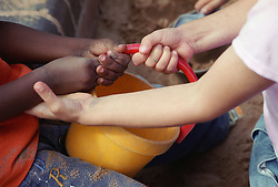 Close up of two nursery school children fighting over bucket in playground sandpit,