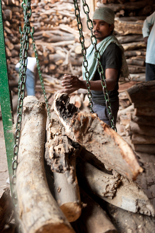 A man weighs wood to be used in a cremation at the Manikarnika cremation ground, Varanasi, India. Photo © robertvansluis.com
