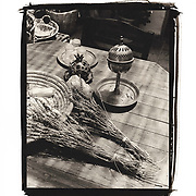 A still life image of objects including some lavender, a spice box, and a basket on a shop table in Tzfat.
