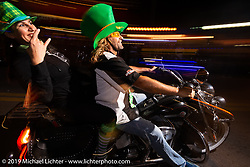 Kelly and Tisa from Vancouver celebrate St Patricks day as they ride down Main Street at night during Daytona Bike Week. Daytona Beach, FL. USA. Saturday March 17, 2018. Photography ©2018 Michael Lichter.