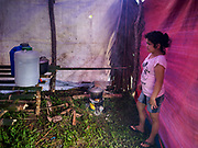 26 JANUARY 2018 - SANTO DOMINGO, ALBAY, PHILIPPINES: A girl cooks lunch in her temporary shelter in a field near Santo Domingo. Mayon Volcano was relatively quiet Friday, but the number of evacuees swelled to nearly 80,000 as people left the side of  the volcano in search of safety. There are nearly 12,000 evacuees in Santo Domingo, one of the most impacted communities on the volcano. The number of evacuees is impacting the availability of shelter space. Many people in Santo Domingo, on the north side of the volcano, are sleeping in huts made from bamboo and plastic sheeting. The Philippines is now preparing to house the volcano evacuees for up to three months.        PHOTO BY JACK KURTZ