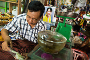 14 JUNE 2013 -  PATHEIN, AYEYARWADY, MYANMAR: A market vendor with a photo of Burmese democracy icon, Aung San Suu Kyi in his shop, prepares an order in the market in Pathein. Pathein is a center of the Burmese umbrella and parasol industry. Most are actually parasols made in the traditional Burmese way using treated paper which is not water proof. Shwe Sar's umbrella's are made with treated cloth and are waterproof. Since US and European sanctions have been lifted businesses in Myanmar have seen an explosion in exports. Shwe Sar exports most of their umbrellas to Europe. Pathein, sometimes also called Bassein, is a port city and the capital of the Ayeyarwady Region, Burma. It lies on the Pathein River (Bassein), which is a western branch of the Irrawaddy River. It's the fourth largest city in Myanmar (Burma) about 190 km west of Yangon.   PHOTO BY JACK KURTZ