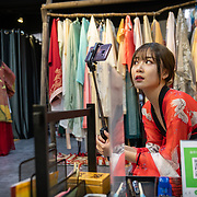 Nai Nai, a 23-year-old live-streamer in Shanghai, China, looks at her camera during a visit to a traditional Chinese dress shop.Nai Nai's fans are mostly Chinese men between 15 and 30 years old who post messages and virtual gifts, visible to everyone logged on to her chatroom. China's livestreaming industry reached 425 million subscribers in 2018 out of a current total internet user base of more than 829 million, according to government statistics cited in Chinese state media. Livestream hosting is an increasingly popular career choice, especially for young Chinese women like Nai Nai.