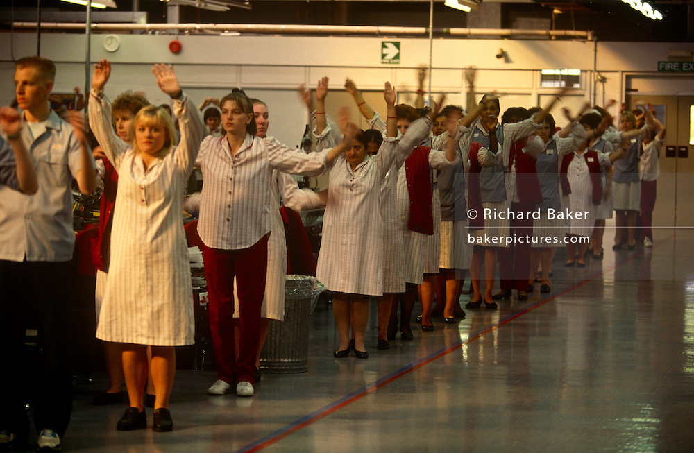 Workers with Alp Electric practice tai-chi before their shift starts at the company's Milton Keynes factory, England. Standing in lines on the factory floor, the British workers stretch their arms overhead to correctly start their working day, according to their Japanese owner's ethos. Alp Electric is one of the world's largest independent manufacturers of electromechanical components, headquartered in Tokyo, Japan. Established in 1948, Alp Electric produces electronic devices, including switchs, potentiometers, sensors, encoders and touchpads. ..