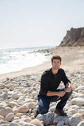 hot All American man kneeling on a rocky beach in Montauk, NY