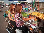 06 APRIL 2010 - NAKHON PHANOM, THAILAND: Thai women on a motor scooter buy mangoes in the market in Nakhon Phanom, Thailand.    PHOTO BY JACK KURTZ