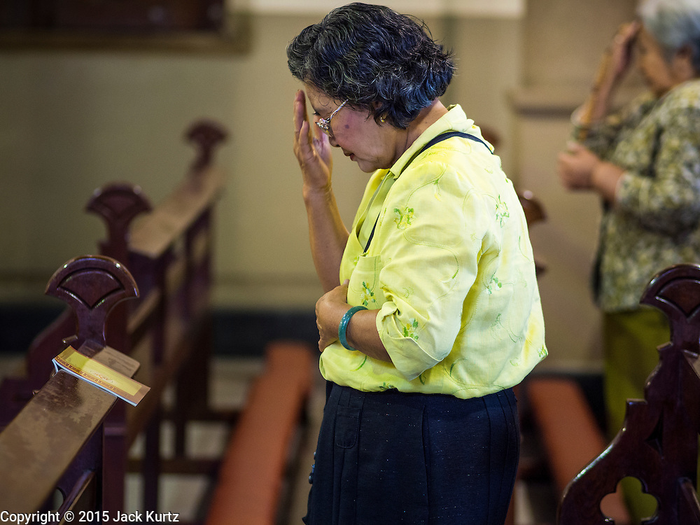 15 FEBRUARY 2015 - BANGKOK, THAILAND: A woman makes the sign of the cross at the beginning of mass in Santa Cruz Catholic Church in the Kudeejeen neighborhood in Bangkok. Santa Cruz church was established in 1770  and is one of the oldest and most historic Catholic churches in Thailand. The church was originally built by Portuguese soldiers allied with King Taksin the Great. Taksin authorized the church as a thanks to the Portuguese who assisted the Siamese during the war with Burma. Most of the Catholics in the neighborhood trace their family roots to the original Portuguese soldiers who married Siamese (Thai) women. There are about 300,000 Catholics in Thailand in about 430 Catholic parishes and about 660 Catholic priests in Thailand. Thais are tolerant of other religions and although Thailand is officially Buddhist, Catholics are allowed to freely practice and people who convert to Catholicism are not discriminated against.      PHOTO BY JACK KURTZ