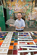 Eztu Glass founder and CEO Brian Yaputra poses for a portrait holding a small stained glass window at his company's factory in Tangerang, near Jakarta, Indonesia, on July 2, 2015.