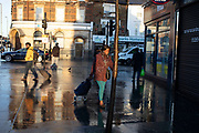Street scene as people go about their daily lives with sunshine and reflections on the pavement on a wet day in Leytonstone in East London, United Kingdom. Leytonstone is an area of East London, and part of the London Borough of Waltham Forest.