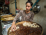 04 OCTOBER 2016 - BANGKOK, THAILAND:  A vendor with Chinese fried tofu snacks at the Vegetarian Festival at the Chit Sia Ma Chinese shrine in Bangkok. The Vegetarian Festival is celebrated throughout Thailand. It is the Thai version of the The Nine Emperor Gods Festival, a nine-day Taoist celebration beginning on the eve of 9th lunar month of the Chinese calendar. During a period of nine days, those who are participating in the festival dress all in white and abstain from eating meat, poultry, seafood, and dairy products. Vendors and proprietors of restaurants indicate that vegetarian food is for sale by putting a yellow flag out with Thai characters for meatless written on it in red.    PHOTO BY JACK KURTZ