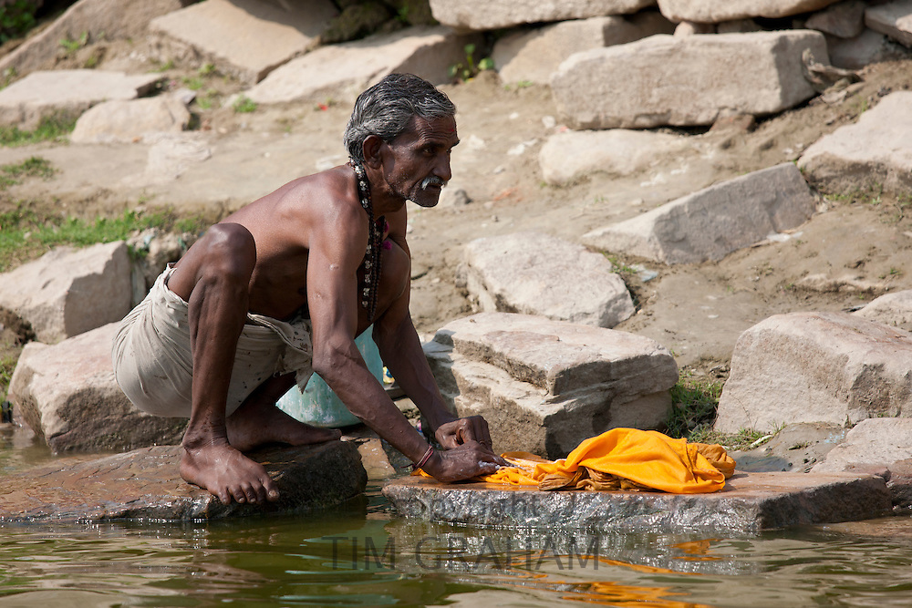 Indian washing clothing in River Ganges using traditional method at Kali Ghat in Varanasi, India