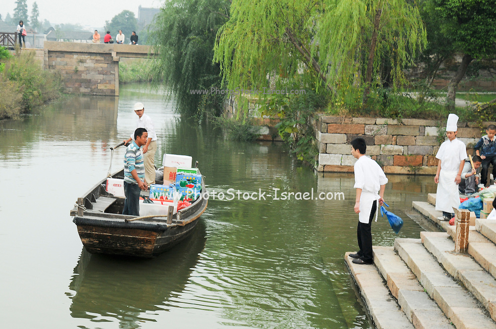 China, Zhejiang Province, Wuzhen a two-thousand-year village proud of it's ancient stone bridges floating on mild water, its stone pathways between the mottled walls and its delicate wood carvings. Bringing supplies to a restaurant by boat