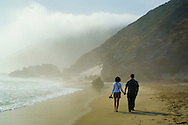 Couple walking together on sand in fog at Pfeiffer Beach, Big Sur Coast, Monterey County, California