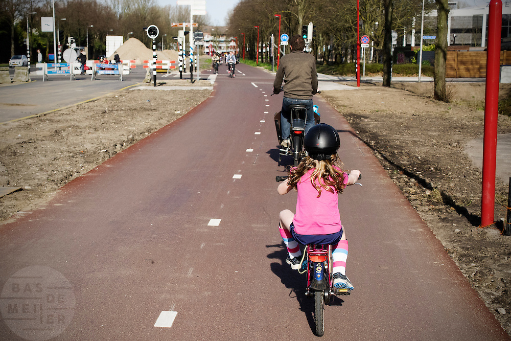 In Utrecht fietst een meisje  met een helm op achterop de bagagedrager over het fietspad tussen het centrum en de Uithof.<br /> <br /> In Utrecht a young girl cycles with a helmet on her head.