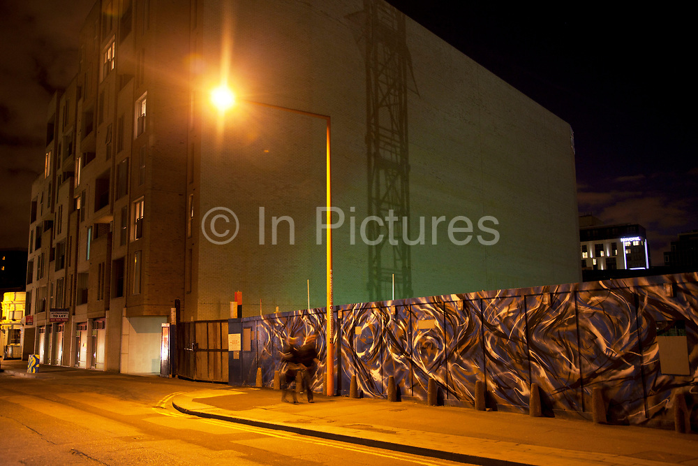 Night scene of urban development in Southwark, London, UK. The image of a crane is thrown in shadow on the side of a large wall.