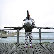 A competitor in the annual Birdman of Bognor event stands on the pier floor boards at Bognor Regis, East Sussex, England. English eccentrics gather annually at the southern seaside town to jump from the pier into the chilly waters of the English Channel. Fun jumpers ?wearing? their aeroplane suits compete for a £25,000 prize for the one to fly 100 metres from the pier platform ? a record not yet achieved. Entrants (who often jump for charity rather than any aeronautical pretensions) include sugar plum fairies, condoms, Ninja Turtles and vampires. The winner was a hang-glider pilot reaching 26 metres but here, a Spitfire pilot sponsored by a milk company eventually dropped vertically. Picture from the 'Plane Pictures' project, a celebration of aviation aesthetics and flying culture, 100 years after the Wright brothers first 12 seconds/120 feet powered flight at Kitty Hawk,1903. .