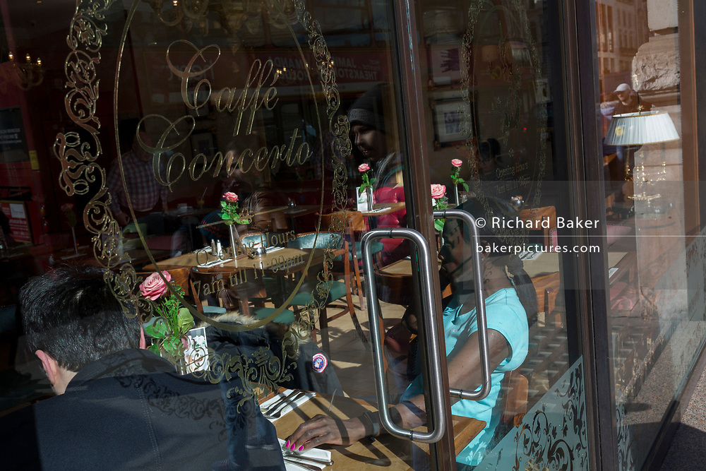 A sunlit Afro-Carribean lady sits in the window of Caffe Concerto, an elegant and prestigious cafe on Piccadilly, on 6th March 2020, in London, England. Caffe Concerto is the purveyors of fine food, champagne, coffee, luxury patisserie, wedding cakes & celebration cakes.