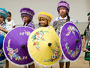 A group of Hmong ethnic minority girls wearing traditional costumes and holding decorative umbrellas before their dance performance at the Women's International Group (WIG) bazaar, Vientiane, Lao PDR. The WIG Bazaar is a charity event aiming to raise funds for projects benefitting Lao women and children.