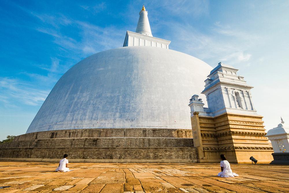 Women sit in quiet reflection at a Buddhist stupa near Anuradhapura.