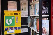 An interior of a former phone kiosk that now serves the local village community with a bring and borrow book library and life-saving defribrillator equipment, on a viillage green in rural Norfolk, on 27th June 2021, in Thursford, Norfolk, England.