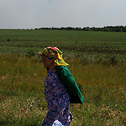 A local woman walks by towards safety near the Malaysia Airlines MH17 crash site in Grabovo, as neighbouring villages get shelled by artillery during combat between the Ukrainian Army troops and separatist rebel groups.