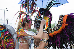 London, August 31st 2015. Two dancers wait for the procession to begin as revellers ignore the inclement weather to enjoy day two of the Notting Hill Carnival.