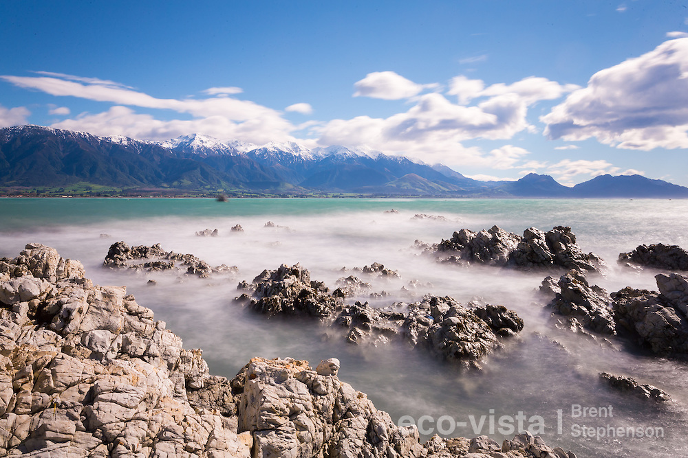 Long exposure during windy rough seas, looking from the rocky limestone shore at Kaikoura across to the Seaward Kaikouras still with remnants of snow. Kaikoura, Canterbury, New Zealand. September.