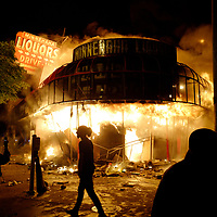 Protesters gather to watch a liquor store burning near the Minneapolis Police third precinct after a white police officer was caught on a bystander's video pressing his knee into the neck of African-American man George Floyd, who later died at a hospital, in Minneapolis, Minnesota, U.S. May 29, 2020. REUTERS/Adam Bettcher