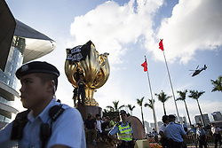 June 28, 2017 - Hong Kong, Hong Kong - Protesters climb to a golden bauhinia sculpture on June 28, 2017 in Wan Chai district of Hong Kong ahead of the upcoming visit of Chinese President Xi Jinping for the 20th anniversary of Hong Kong return to China. (Credit Image: © Chan Long Hei/Pacific Press via ZUMA Wire)