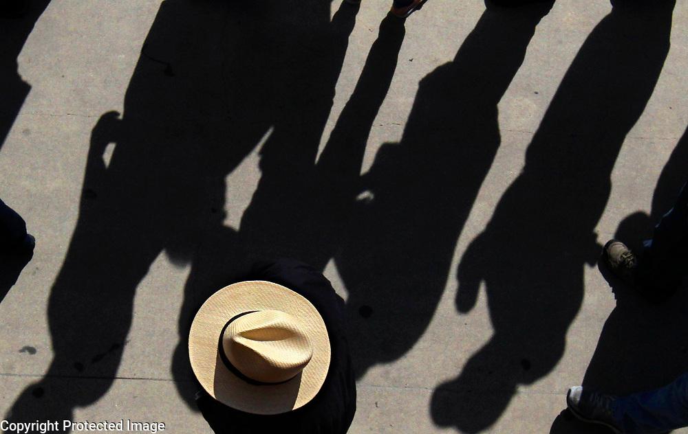 Long afternoon shadows fill the main walkway at the Santa Cruz Beach Boardwalk in Santa Cruz, California as a man wearing a fedora makes his way through the crowds at the annual Clam Chowder Cook-Off.<br /> Photo by Shmuel Thaler <br /> shmuel_thaler@yahoo.com www.shmuelthaler.com