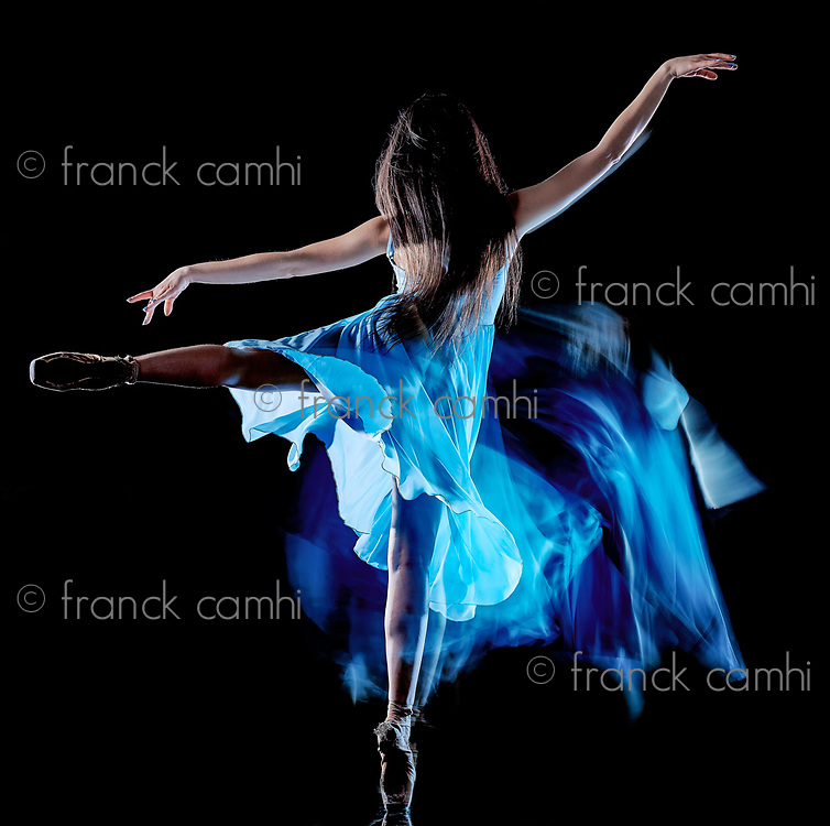one caucasian young woman ballet dancer dancing isolated on black background with  light painting motion blur speed effect