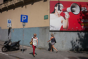 Women pass each other underneath a large advertising billboard featuring a shouting model holding a loudhailer, on a street corner, on 20th July, in Porto, Portugal. There is a message in this ad campaign of volume - to brashly get ones message heard.