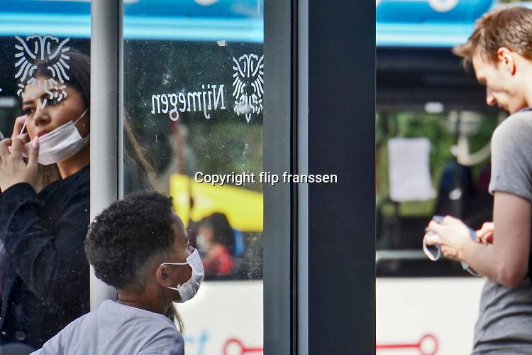 Nederland, Nijmegen, 20-6-2020  Mensen in de bus dragen een gezichtsmasker . Het is verplicht in het openbaar vervoer volgens de noodverordening die de regering heeft uitgevaardigd om een tweede golf van coronabesmetting te voorkomen .Foto: Flip Franssen