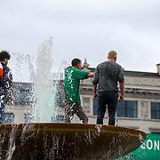 Three guys jump up the fountain at the London's St Patrick's Day 2017 in Trafalgar Square on 19th March 2017. by See Li
