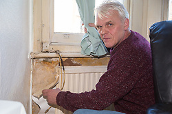 Retired James Gosling, 58, who is involved in a long running dispute with Camden council that began when his flat was flooded with sewage, shows the damp patch by his radiator which includes mould that he says has made him ill. West Hampstead, London, October 25 2018.