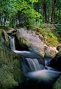 Small waterfall feeds down from an small, upper lake - Quebec, Canada