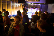 Audience listening carefully to a poet delivering her spoken words at a poetry reading at The Social, a small music and arts venue in central London, UK.