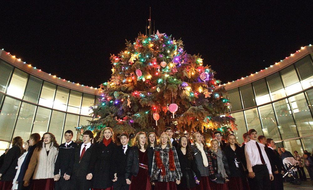 Decorated with over 3,000 lights, ornaments made by area elementary school students and surrounded by Northwest High School's 14 Karat Gold Show Choir, the 40-foot community Christmas tree is finally illuminated Tuesday evening outside City Hall.Mayor Jay Vavricek and other city officials past and present attended the twentieth annual event which featured cupcakes, candy and singing. (Independent/Matt Dixon)