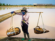 28 MARCH 2018 - BAN LAEM, PHETCHABURI, THAILAND: A worker before her shift shift during the 2018 salt harvest in Petchaburi province, about two hours south of Bangkok. Sea salt is made in provinces south of Bangkok by flooding fields with ocean water after the rainy season. As the fields dry out from evaporation, workers go into the fields and gather the salt left behind.          PHOTO BY JACK KURTZ