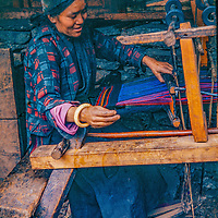 A Nepali woman weaves on a treadle loom at her home in a in a village in the foothills of Nepal's Himalaya.