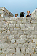 Two children (9 years old and 5 years old) looking over stone wall parapet, beside cannon. Fortress Lovrinjenac (Fort of Saint Lawrence), Dubrovnik old town, Croatia
